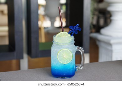 Closeup glass of Iced blue hawaii soda with lemon on table and on blurred background, Summer Cocktail or Tropical Mocktail.