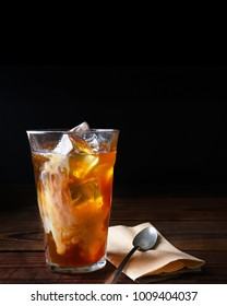 Closeup of a glass of iced coffee on a dark wood table. Fresh poured cream is permeating through the glass with a napkin and spoon lay next to the glass. Vertical with copy space.