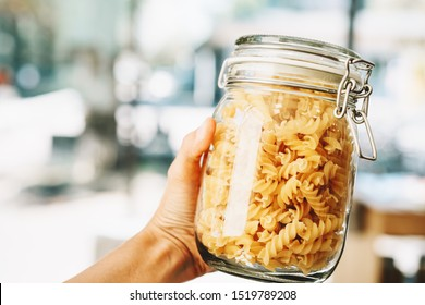Close-up of glass jar with pasta in hand on the background of zero waste shop interior. Image of shopping at small businesses. New trend alternative buying. Concept of plastic free grocery store.