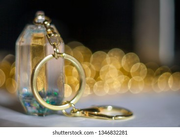 Closeup glass key chain with gold chain and ring on a blurred background with a beautiful bokeh from the beads