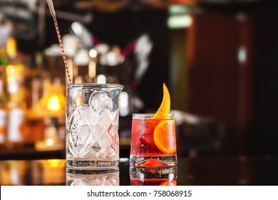 Closeup glass of negroni cocktail decorated with citrus and decanter with ice at bar stand festive background.