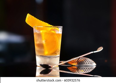 Closeup glass of old fashioned cocktail decorated with orange at bar counter background.
