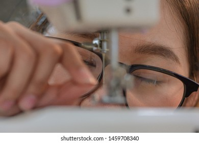 Closeup of glass on eye of sewer or housewife trouble and hard try to leading thread insert to the pin or needle of the sewing machine, old age eye of woman difficult in small tailoring works