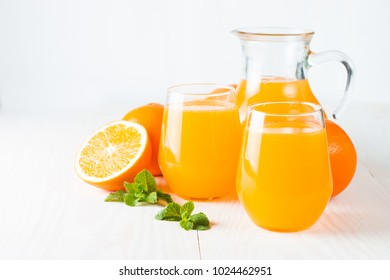 Close-up of a glass of orange juice with oranges fruits on wooden and stone background. Vitamins and minerals. Healthy drink and beverage concept.