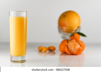 Close-up of glass of orange juice. Sweet orange, tangerines with leafs on a white background