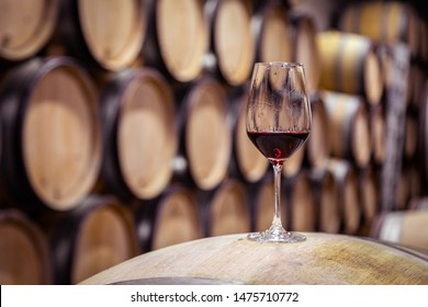 Closeup glass with red wine on background wooden wine oak barrels stacked in straight rows in order, old cellar of winery, vault. Concept professional degustation, winelover, sommelier travel