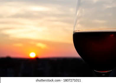 Close-up glass with red wine on a blurred background with copy space. Part of a wine glass on a sunset sky background. Sunset. Beautiful sunset with a glass of wine in the foreground.