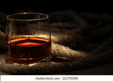 Closeup of glass of rum near rope on dark background