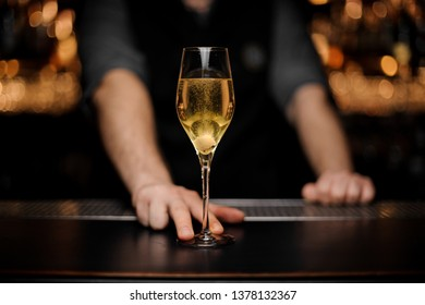 Close-up of glass with sparkling wine on the bar counter in the male bartender's hands