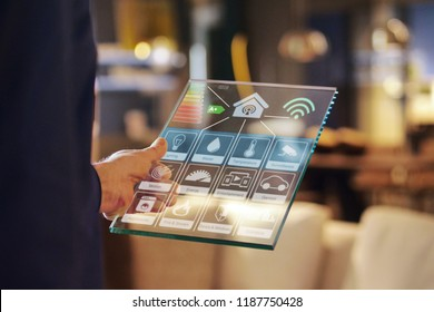 Close-up of a glass tablet controls all the functions of the house such as wi-fi, heating, lighting, television through holography. Concept of, home automation, automations, future, technology.