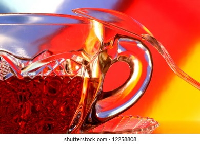 Close-up of glass teacup, spoon and saucer  against many colored abstract background.