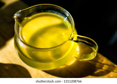 Closeup of glass teapot on wooden table in dark room with sunlight from window, filled with Japanese green or oolong yellow tea color sencha