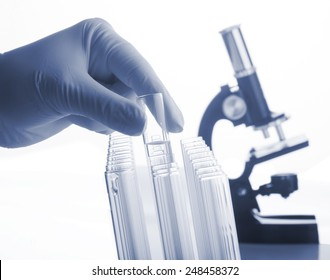 Closeup of glass test tubes and laboratory microscope on a white background.