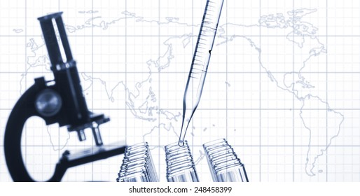 Closeup of glass test tubes and laboratory microscope on a world map background.