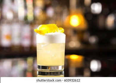 Closeup glass of whiskey sour cocktail decorated with lemon at bar background.