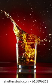 Close-up of glass with whiskey splash.On red background.Concept alcohol splash