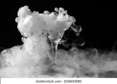 Closeup glass with white fog at dark background. Chemical reaction of dry ice with water.