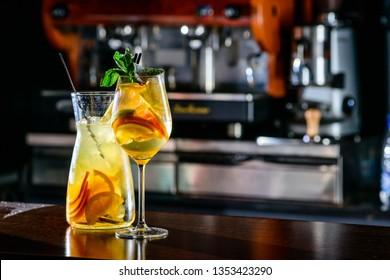 Closeup glass of white sparkling wine sangria decorated with citrus slices at bright bar counter background. Sangria Spanish white wine mixed in decanter Copy space on bar blurred background