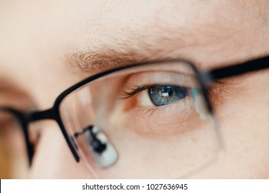 Close-up of glasses and blue eye of man. Concept businessman, student, read, reflect, think.