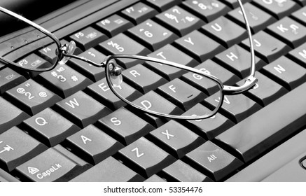 Closeup of glasses lying on the laptop