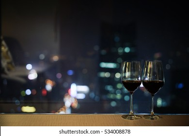 Closeup of a glasses of red wine at windowsill, against night view of urban city sky line blurring lights.