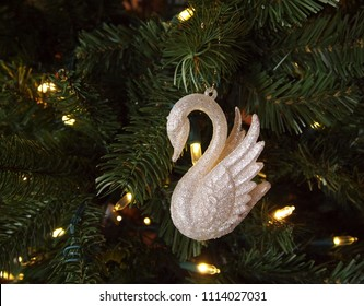 Closeup of a glittery white swan ornament hanging in a green Christmas tree with twinkling white LED string lights.