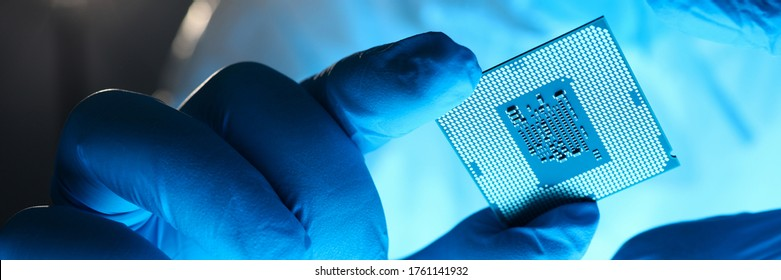 Close-up gloved hands holding detail microchip. Man in special uniform shows microprocessor chip. Production technology hitech. Repair microprocessor electronics electrical equipment.