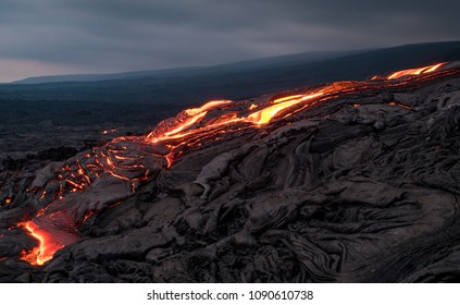 Closeup of glowing lava flow from Puu Oo in the evening on the Pali in Kalapana, Big Island, Hawaii.