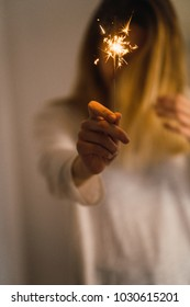 Close-up of glowing sparkler in hand of young anonymous girl.