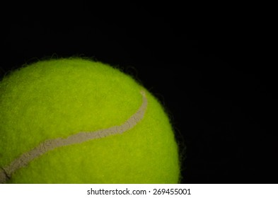 A close-up of the glue on a single tennis ball against a solid black background.