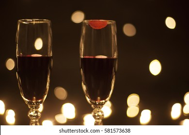 Closeup goblets with red wine imprint lipstick on the glass. Filled wine glasses Isolated on black background with bokeh effect