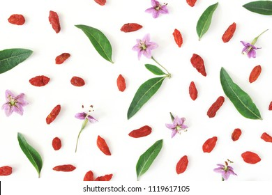 Closeup of Goji berries, Lycium barbarum. Dried Asian fruit, leaves and blossoms isolated on white wooden background. Healthy superfood. Floral pattern. Flatlay, top view.