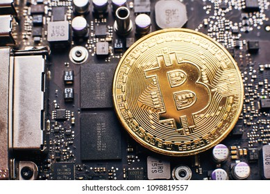 Close-up of gold bit coin, computer circuit board with bitcoin processor and microchips. Electronic currency, internet finance ?rypto currency. Bitcoin mining.