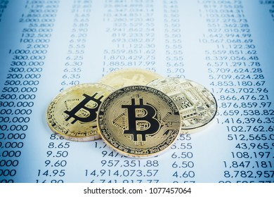Closeup gold bitcoins cryptocurrency on transaction paperwork reports, blue filter. Electronic digital money transfer through blockchain, cyber verify code, decentralized, proof of work concepts.
