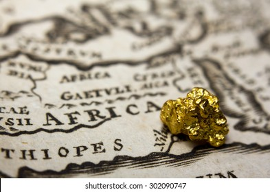 Close-up of a gold nugget on top of an old map of Africa