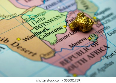 Close-up of a gold nugget on top of an old map of South Africa