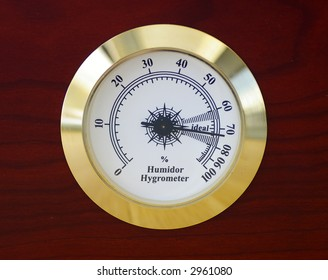 Closeup of a gold rimmed humidor hygrometer on a cherry wood cigar humidor.  Gauge reads approximately 73% humidity, within the 'ideal range' for storing and aging cigars.