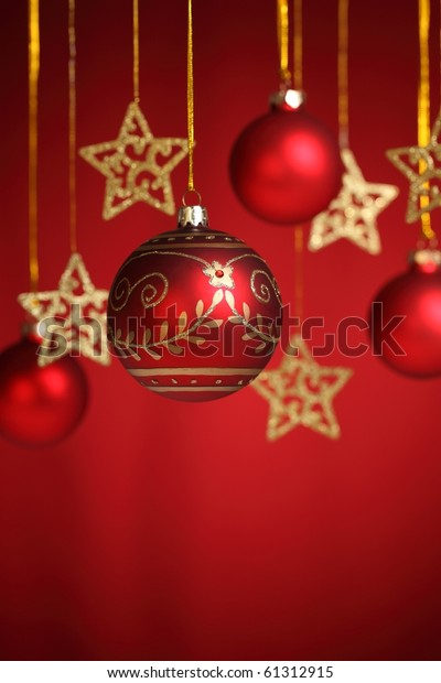 Closeup of gold star and christms bauble on red  background.