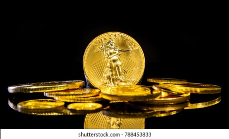 closeup of golden american eagle coin on black background with many golden coins at bottom