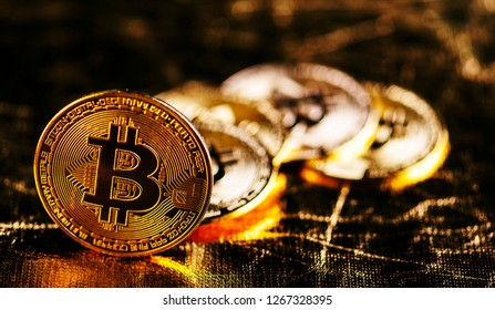 Closeup of golden bitcoin BTC cryptocurrency over black and gold background. Virtual money and blockchain concept.