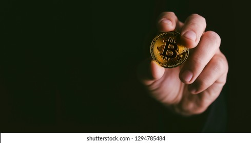 Closeup of golden bitcoin BTC cryptocurrency in hand over dark black background. Man holding golden crypto coin. Virtual money and blockchain concept.