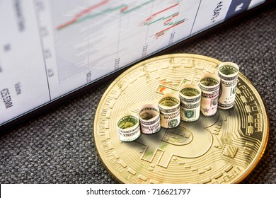 closeup of golden bitcoin coin with a chart reflection on its surface with green and red bars and rolls of dollar banknotes forming rising steps