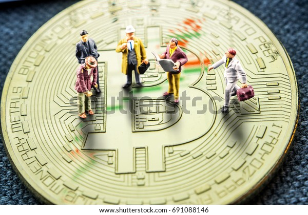 closeup of golden bitcoin coin with a chart reflection on its surface with green and red bars and miniature business men figurines having a meeting