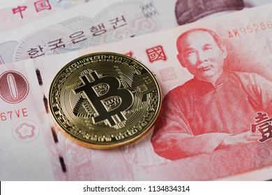 Close-up of a golden bitcoin on 100 New Taiwan Dollar bill. Cryptocurrency or Asia economy business concept.