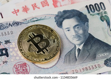Close-up of a golden bitcoin on 1000 Yen banknote background, Cryptocurrency or Asia economy business concept.