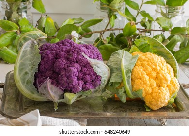 closeup Golden Cauliflower and fresh purple cauliflower - raw, healthy food on a silver platter