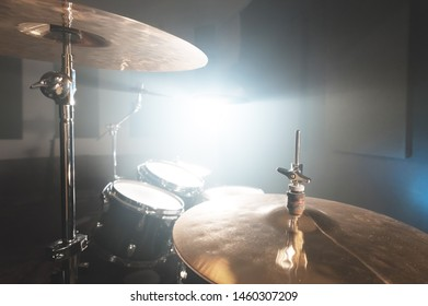 Close-up Golden cymbals Modern drum set prepared for playing in a dark rehearsal room on stage with a bright spotlight. The concept of percussion musical instruments