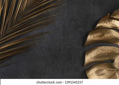 Closeup of golden palm and monstera leaves on abstract dark grey textured background. Tropical conceptual elegant trendy summer background. Flat lay. Copy space.