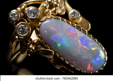 Closeup of a golden ring with a colorful opal gemstone