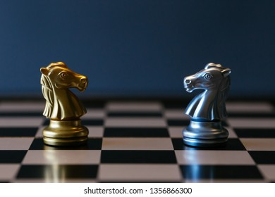 Closeup golden and silver horse knights places against each other on chessboard against gray background